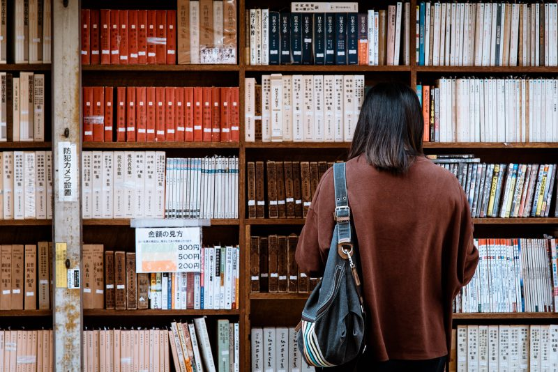 Woman Wearing Brown Shirt Carrying Black Leather Bag on Front of Library Books.