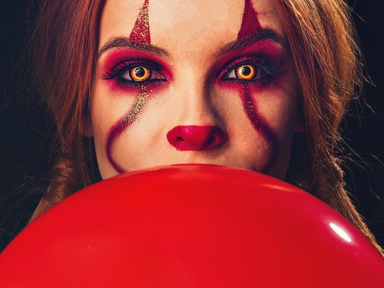 Girl with clown makeup holding a red balloon