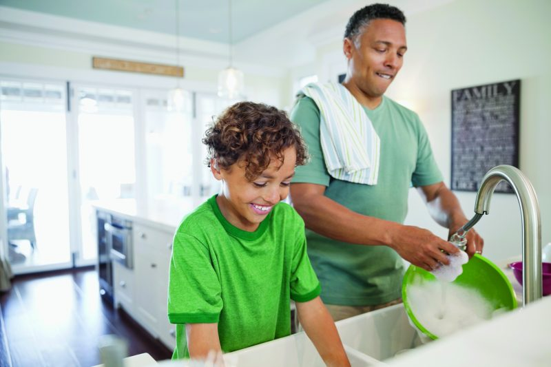 Father and son washing dishes together positive parenting