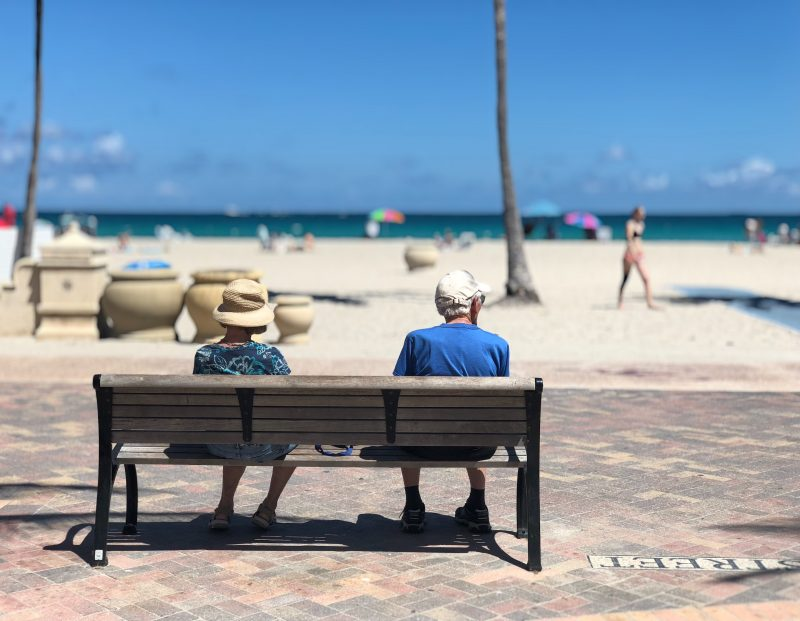 Image of retired couple sitting by the shore.
